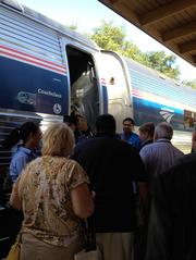 Attendees gather to board the Amtrak train in DeLand to begin the SunRail sneak peek ride by the Orlando Regional Realtors Association.