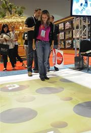 Luna Tolunay of Fun Planners tests out an interactive, ceiling projected game system on the IAAPA exhibitor floor.