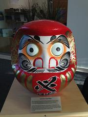 The Daruma doll is a red ceramic statue. In Japanese culture, when a group sets a high goal, they call upon the Daruma doll.