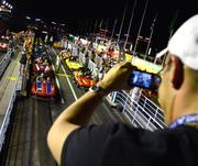 Philip Jacoby takes a photo of his family on the Grand Prix Raceway. The Jacobys had no idea their vacation coincided with the all-night event, but they were up for the challenge of being up until 6 a.m.