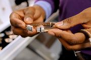 Green demonstrates the clasp on a men's bracelet he recently made.
