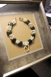 Green also creates jewelry as framed art pieces.