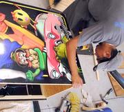 Anthony Perez fixes an arcade game in the production area at Fun Planners.