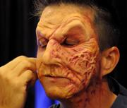 "A model undergoes the transformation into a ""scare-actor"" during a makeup and prosthetics demonstration at the Halloween Horror Nights 2012 media preview."