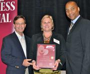 Nicole Parkerson, center, and Doug Worswick, center, of Certified Slings & Supply accept the first place award in the category of five to 99 employees from Tony Jenkins of Blue Cross Blue Shield of Florida.