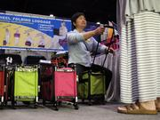 Susan Lee of TUTTO, a luggage company, demonstrates the durability of a new line of 4-wheeled bags for a convention guest.
