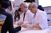 Convention guests get a blood sugar test at the Novo Nordisk healthcare company booth.