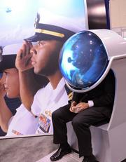 A conventioner watches a Naval recruiting film projected on a head piece dome at the US Navy booth.