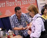 A conventioner gets a sample of a new skin therapy treatment at the Infinite Aloe table.