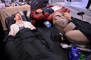 Conventioners are hard at work testing a new line of massage chairs by the Infinity company.