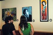 Patrons browse the extensive collection of art on the walls at On The Rocks.