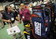Guests notice more themed merchandise at an NFL golf bag display by the Team Golf company.