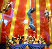Trapeze artists soar above the crowd in the miniature circus environment.