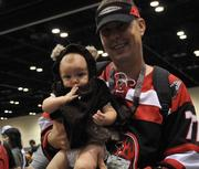 Marc Leduc of Jacksonville holds his 5-month-old daughter Sophia, who is dressed as an Ewok from Return of the Jedi, while waiting in line to enter the exhibit hall at Star Wars Celebration 6.