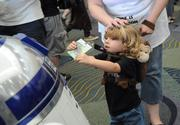 Two year old Coraline Rogers of Tennessee shows off her Star Wars Celebration 6 day pass to a passing R2D2 in the halls of Orange County Convention Center.