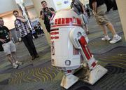 Cole Horton, at left, of the Droid Builders club, nonchalantly pilots an astromech droid via remote control at Star Wars Celebration 6.