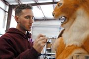 Robert Bennett applies a base color before airbrushing the spots on an animatronic leopard's coat at Florida Creative Industries.