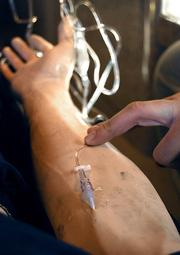 A needle is inserted into a sim patient used for intravenous training at the Emergency Medicine Learning & Resource Center.