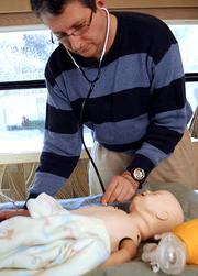 Sims come in all sizes. Eric Dotten of the Emergency Medicine Learning & Resource Center works with an infant model.