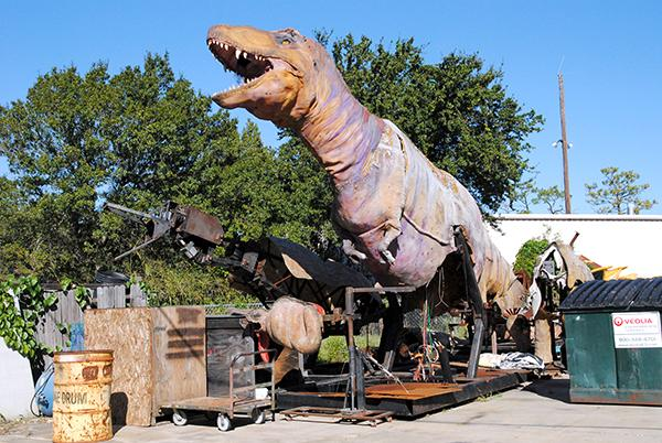 A full size tyrannosaurus rex stands outside the production building at Florida Creative Industries.