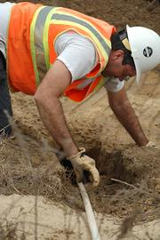 Environmental Scientist Joel Johnson measures the burrow with two 10-foot poles to see how far it goes.