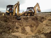 As the search for the burrow resident continues, a second backhoe joins the dig.