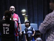 Fans stand in line for a photo next to the NBA championship trophy, on display at the Jam Session.