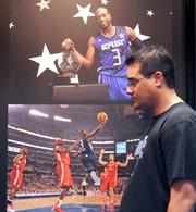 Shawn Blas of Orlando checks out a gallery of photography from past NBA All Star events at the NBA Jam Session at Orange County Convention Center.