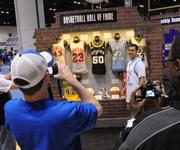 Fans take pictures beside NBA star jerseys and other memorabilia at an NBA Hall Of Fame exhibit at the NBA All Star Jam Session.