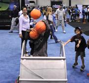 Young fans try and catch as many basketballs as they can from a robotic ball-tossing exhibit sponsored by the Embry Riddle Robotics Association at the NBA All Star Jam Session.