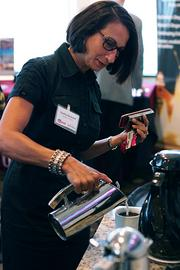 Cynthia Blackwell of BlackRain Partners pours herself a cup of coffee prior to the panelists speaking at Orlando Business Journal's Power Breakfast on the modeling and simulation industry.