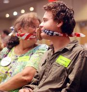 """EPA supporters who felt they weren't represented during the hearing wore American flag gags and stickers that read """"slime crimes."""""""