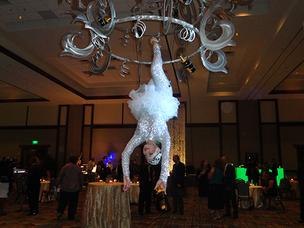 A chandelier acrobats pour champagne for guests.