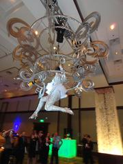 A chandelier acrobat pours champagne for guests.