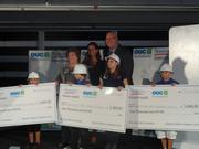 Nemours and Orlando Utilities Commission officials present checks to the four winners of an Orlando Utilities Commission Light Up Nemours contest. Each check is worth $1,000 which is donated to the school each child attends.