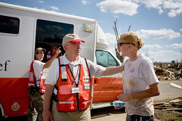 The American Red Cross is increasing its fleet of emergency trucks with vehicles built by Wheeled Coach in Winter Park. Trucks distribute supplies in disaster areas. Pictured: Volunteer Anthony Muscolino with Amanda Bell Armstrong in Concord, Ala., following tornadoes in May.