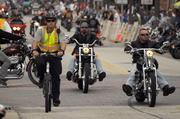 A police patrolman on a bicycle rides along side bikers as Main Street crowds build on the first day of Daytona Beach Bike Week.