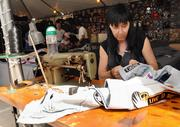 Patricia Alexander sews a patch onto a customer's jacket at the Patch Stop booth on Main Street.