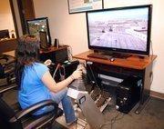 Stephanie Encarnacion of Dignitas demonstrates a heavy equipment training simulator.