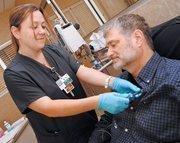 Nurse Stefanie Cepeda prepares cancer patient John Ostenburg for chemotherapy.