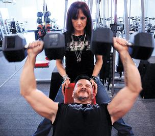Laura Allen, owner of Sweat, pushes Edward Woodill III to the limit in his workout.