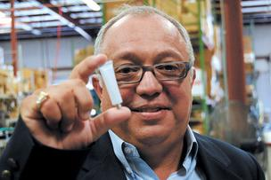 Edgardo Rodriguez of Hernon Manufacturing shows a tube of his company's adhesive.