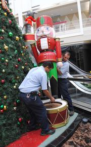 Workmen install decorations at Orlando Fashion Square mall.