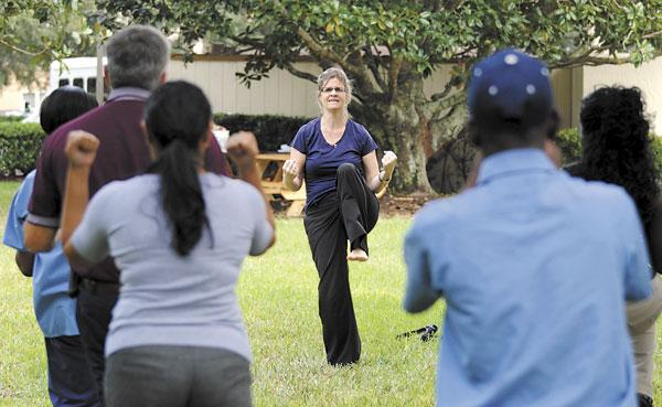 Clarion Inn Lake Buena Vista General Manager Jennifer Rice, center, leads a group fitness class for employees on hotel property.