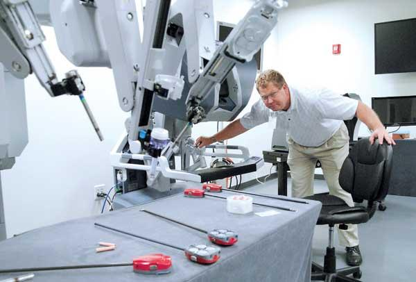 Todd Larsen, director of the Mimic Training Center at the Nicholson Center with the da Vinci surgical system