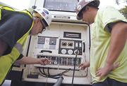Mike Powers (L) and Brian Northcott of Tri-City Electrical Contractors check a backup generator.