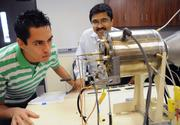from left: UCF aerospace engineering student Sergio Arias and professor Jay Kapat inspect a jet engine model that uses fuel made from algae at the UCF Center for Advanced Turbine and Energy Research.