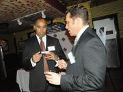 from left: Shay Harold of PNC Bank and Steven Woodell of Hancock Bank exchange business cards.