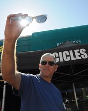 Guy Collier of the Colorado-based Icicles Sunglasses Co. shows off some inventory to passing bikers on Main Street during Biketoberfest 2012.