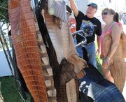Customers browse a selection of alligator hide for custom bike seats at a vendor on Beach Street during Biketoberfest 2012.